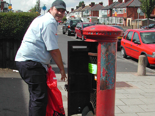 Postman emptying Post Box