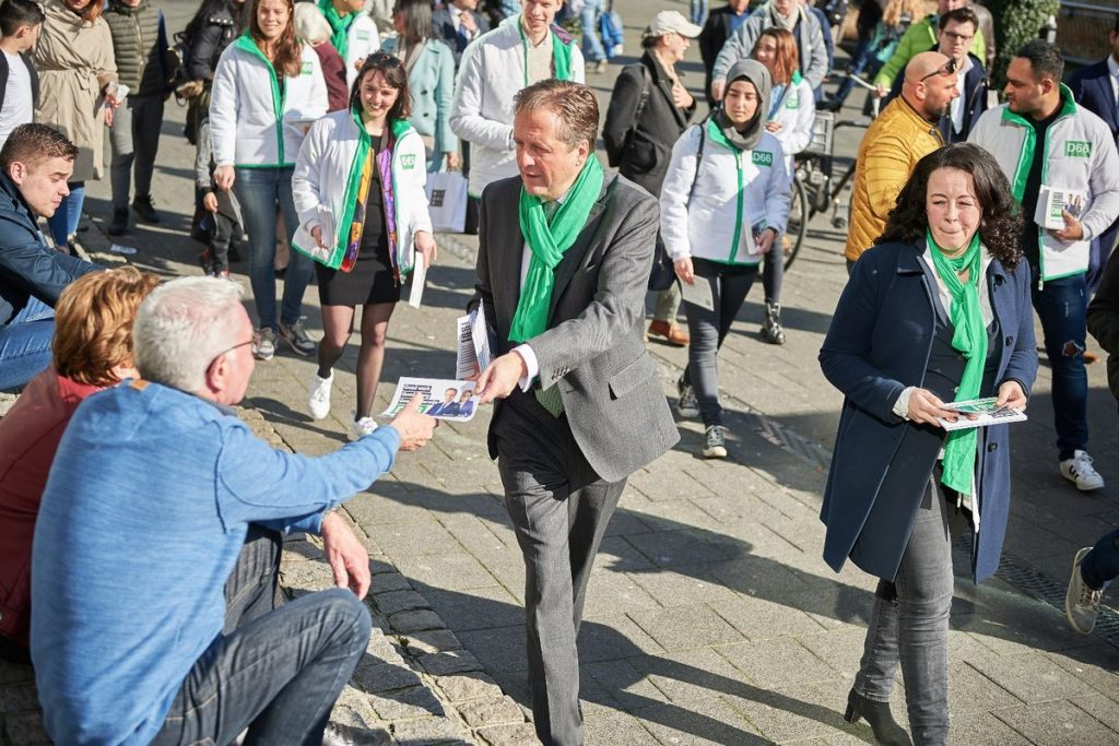 A picture of the Dutch party D66 delivering leaflets wearing matching scarfs